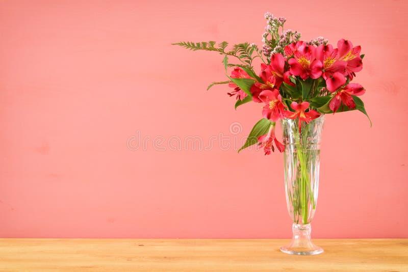 bouquet d'été des fleurs rouges et roses dans le vase au-dessus de la table en bois et du fond en pastel photographie stock