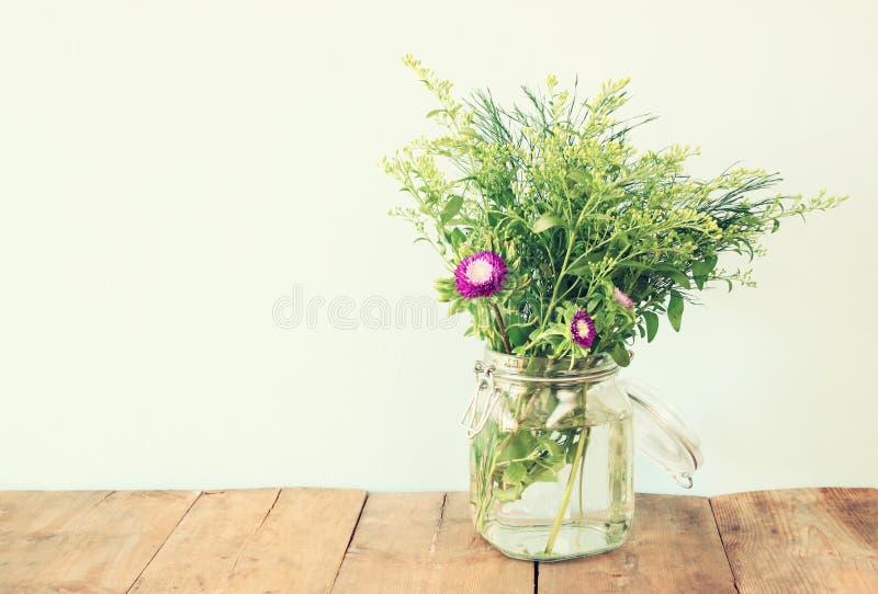 Bouquet d'été des fleurs sur la table en bois avec le fond en bon état image filtrée par vintage photographie stock