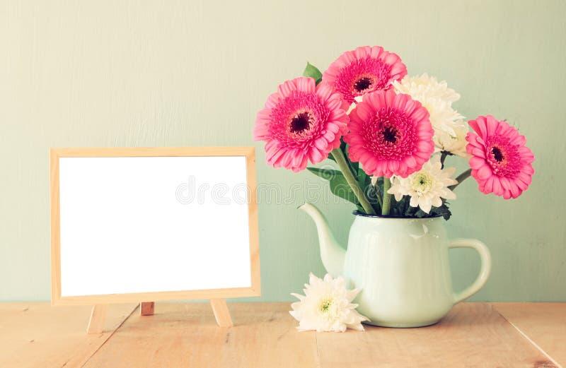 Bouquet d'été des fleurs sur la table et le tableau noir en bois avec la pièce pour le texte avec le fond en bon état image filtr photo stock