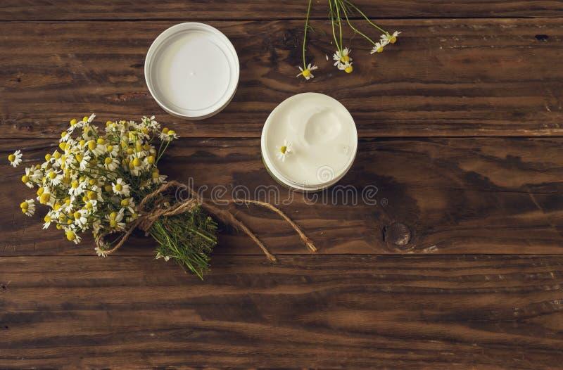 Bouquet de camomille et crème corporelle parfumée sur une table en bois image libre de droits