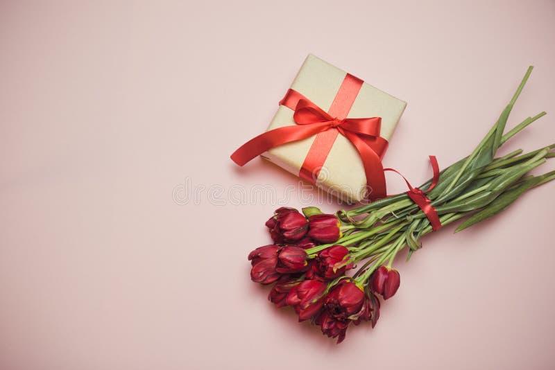 Bouquet de composition de tulipes rouges avec boîtes-cadeaux ruban satiné sur fond rose avec espace vide au centre, vue supérie photographie stock