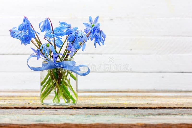 Bouquet de fleur de jacinthe des bois dans un vase sur la table sur un fond blanc avec l'espace de copie photo stock