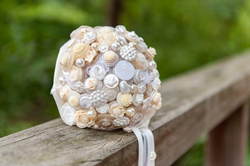 Bouquet de fleur de jeune mariée sur le guidon de pont en bois photographie stock