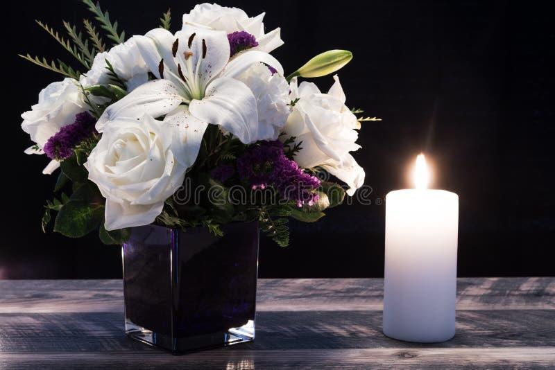 Bouquet de flores brancas em vaso roxo, vela branca em pranchas de madeira Vintage home decor black tonts Cartão de pêsames fotos de stock