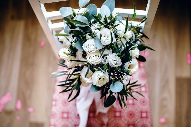 Bouquet de jeune mariée de mariage des eustoms sur la chaise photo stock