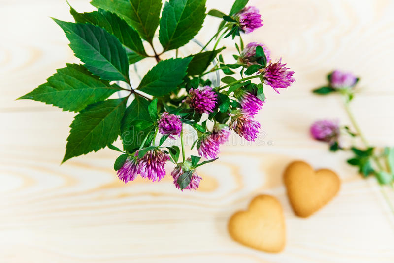 Bouquet de la fleur, biscuits en forme de coeur sur le backgro en bois de table image libre de droits