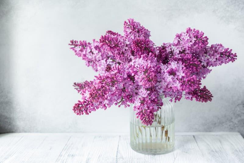 Bouquet de lilas dans un vase en verre devant le mur en pierre avec l'espace pour votre style rustique des textes photo stock