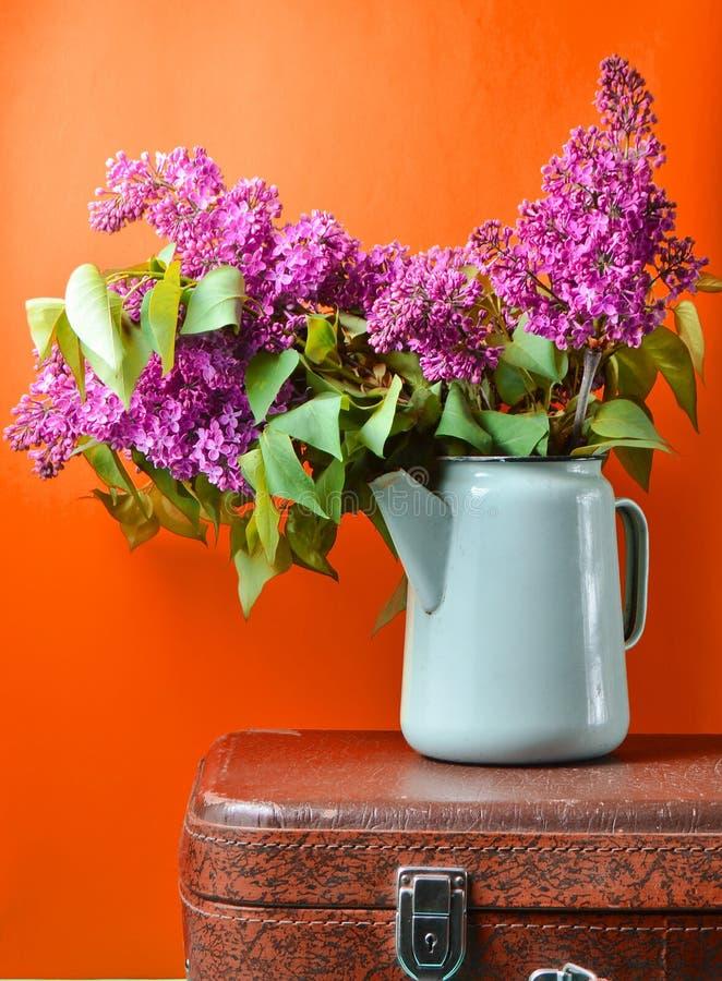 Bouquet de lilas dans une vieille théière émaux sur la valise de cru sur le fond jaune La rétro de style toujours vie photographie stock libre de droits
