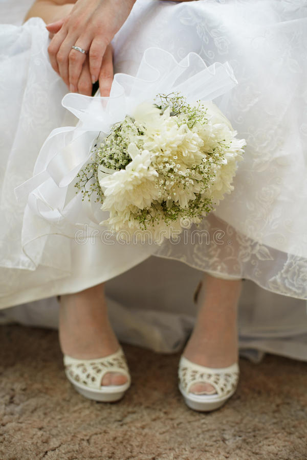 Bouquet de mariée contre la robe et les chaussures image stock