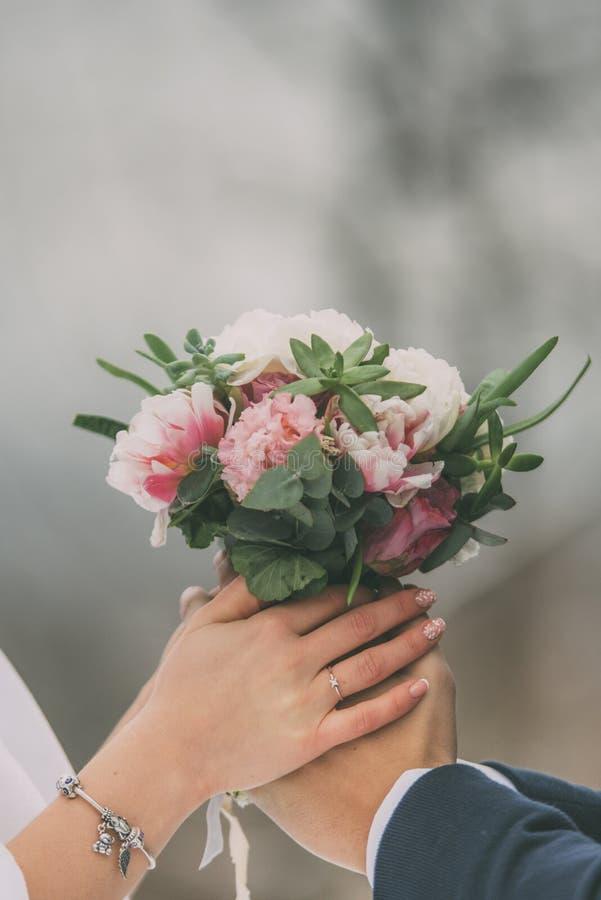 Bouquet de mariage avec des anneaux dans des deux mains photographie stock