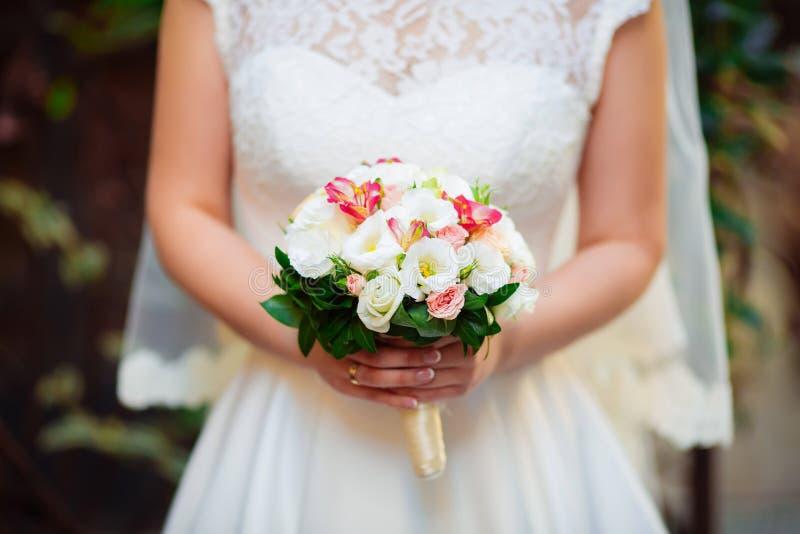 Bouquet de mariage dans les mains d'une jeune mariée photographie stock libre de droits