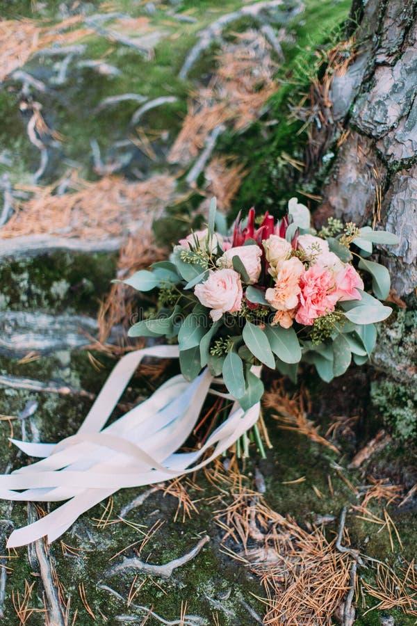 Bouquet de mariage des fleurs colorées décorées des rubans sur l'arbre image stock