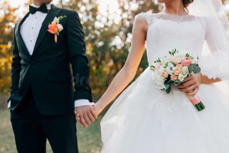 Bouquet de mariage La jeune mariée brouillée avec dedans une robe blanche et le marié dans le smoking tiennent des mains Foyer mo photographie stock libre de droits