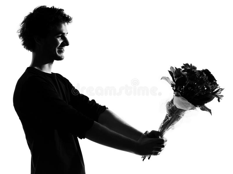 Bouquet de offre de fleurs de silhouette de jeune homme photographie stock
