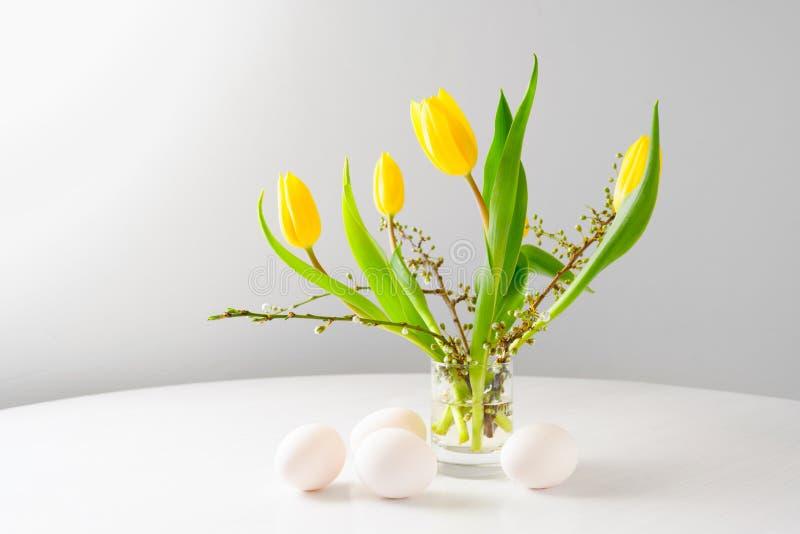 Bouquet de Pâques avec les tulipes et les branches jaunes de ressort en verre d'Al quatre oeufs sur une table blanche sur un fond image stock