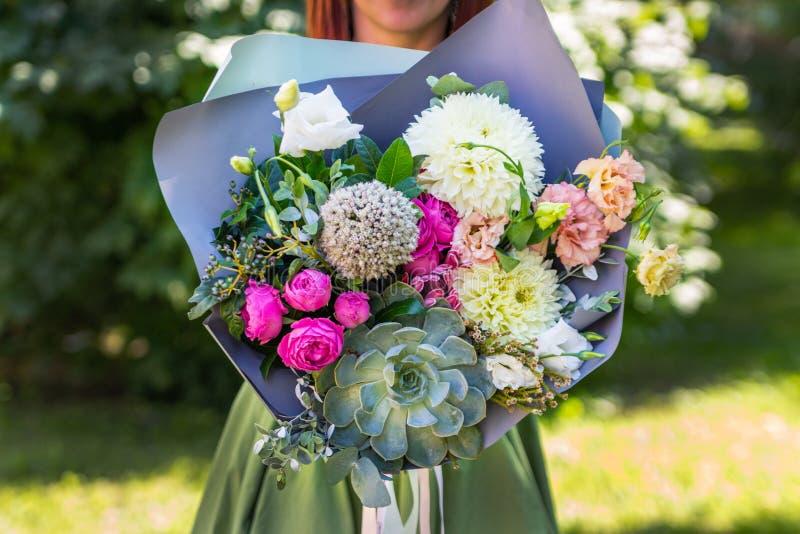 Bouquet de plan rapproché La fille tient un bouquet d'écoulement frais image stock