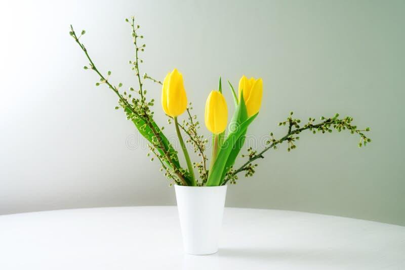 Bouquet de ressort, vase avec les tulipes jaunes et branches sur une table blanche sur un fond gris bleu avec l'espace de copie photographie stock libre de droits
