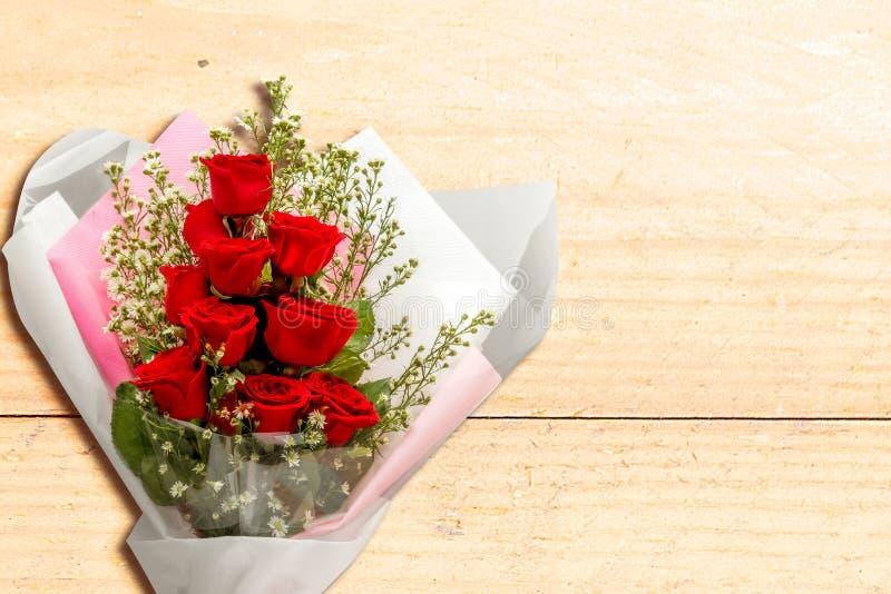 bouquet de rosas vermelhas envolto em papel em mesa de madeira imagens de stock