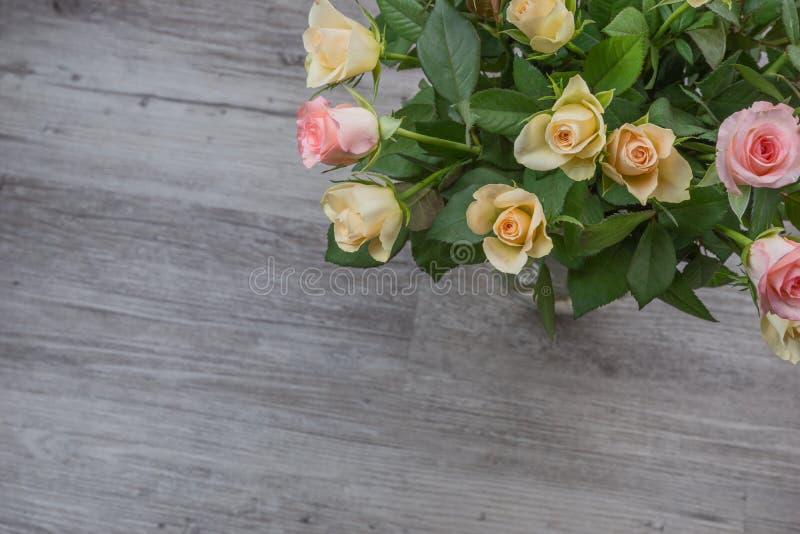 Bouquet de roses roses et jaunes au-dessus de table photographie stock