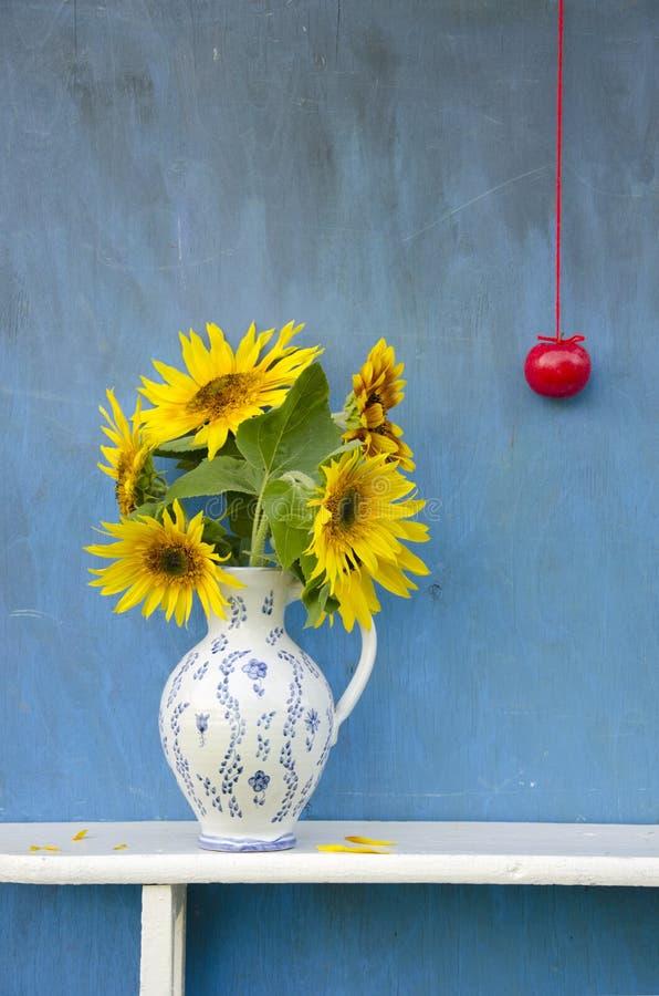 Bouquet de tournesols d'été beau dans le broc élégant avec la pomme rouge photographie stock libre de droits