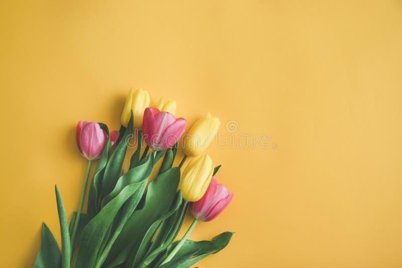 Bouquet de tulipas frescas sobre fundo amarelo, vista superior, camada plana foto de stock royalty free