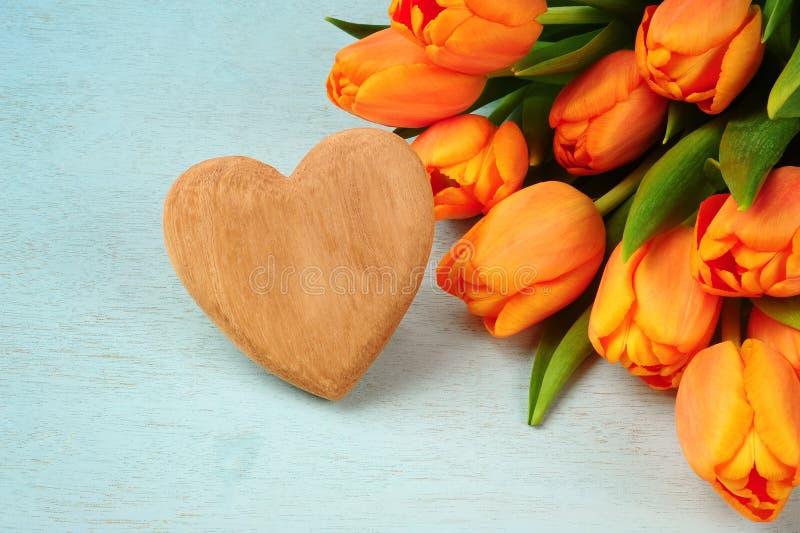 Bouquet de tulipe et coeur en bois image stock