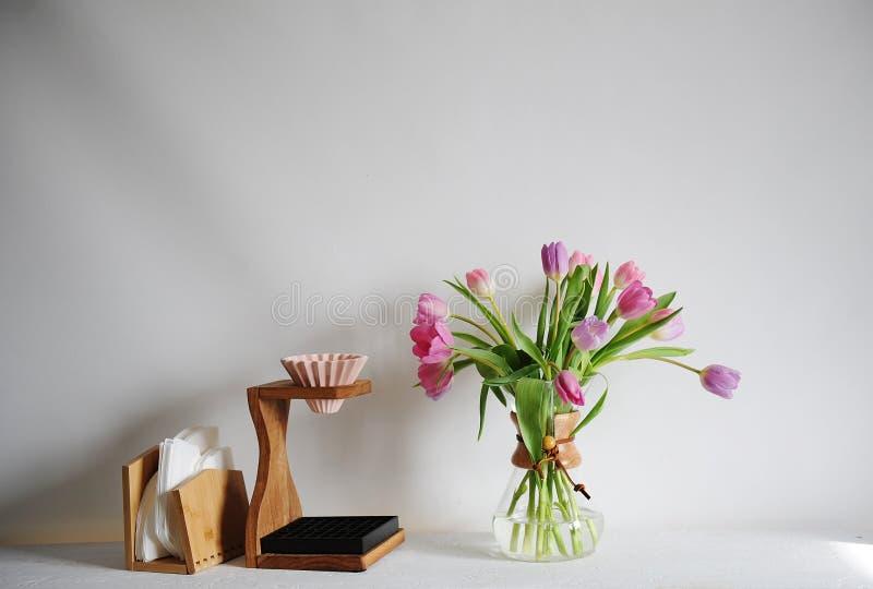 Bouquet de tulipes de fleurs dans le décanteur de café sur la table blanche Brassage manuel avec l'origami dispositif d'écoulemen photographie stock