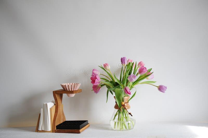Bouquet de tulipes de fleurs dans le décanteur de café sur la table blanche Brassage manuel avec l'origami dispositif d'écoulemen photos libres de droits