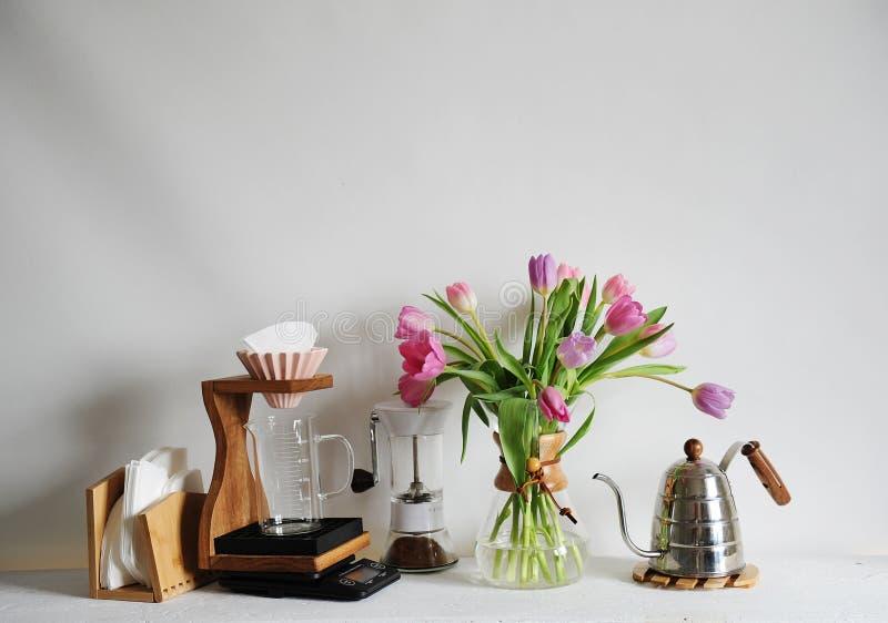 Bouquet de tulipes de fleurs dans le décanteur de café sur la table blanche Brassage manuel avec l'origami dispositif d'écoulemen image stock