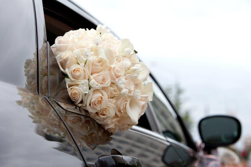 Bouquet de voiture et de jeunes mariées dans une fenêtre de voiture photo stock