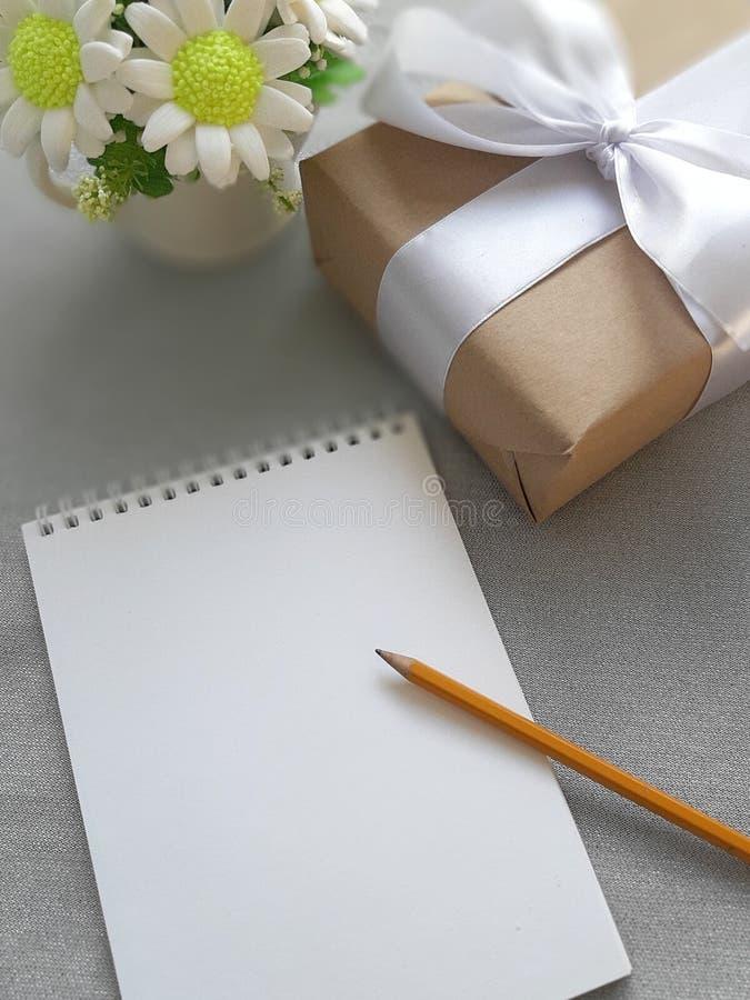 Bouquet des fleurs, boîte-cadeau, bloc-notes de papier blanc sur le fond gris photographie stock