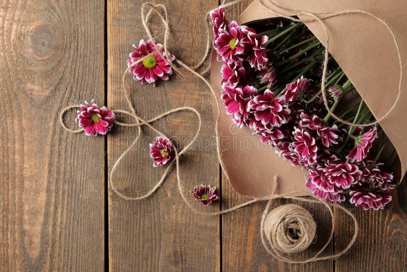 bouquet des fleurs d'automne des chrysanthèmes en papier de métier sur une table en bois brune image stock
