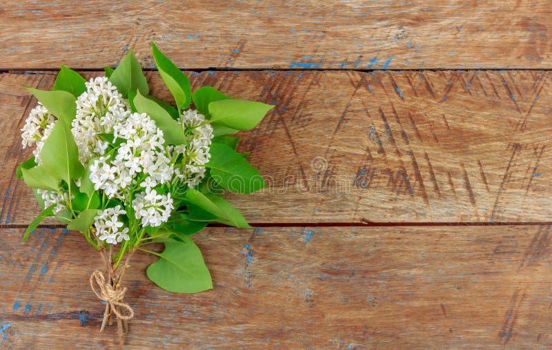 Bouquet des fleurs lilas blanches sur le rétro fond grunge en bois photos stock