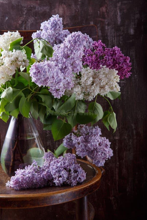 Bouquet des fleurs lilas sur la vieille chaise de cru La vie toujours sur le fond foncé images libres de droits