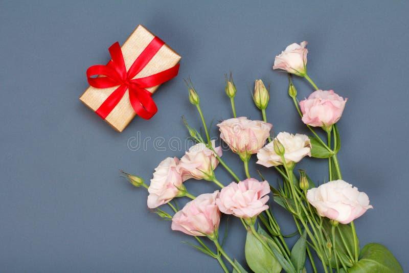 Bouquet des fleurs roses avec les feuilles et le boîte-cadeau avec le ruban rouge sur le fond gris Vue supérieure photo stock