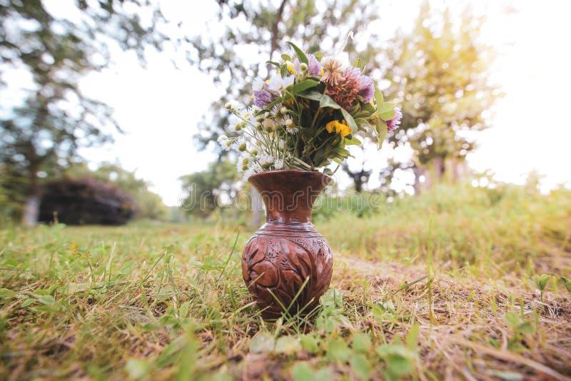 Bouquet des fleurs sauvages sauvages colorées dans un pot d'argile cassé étendu sur l'herbe images stock