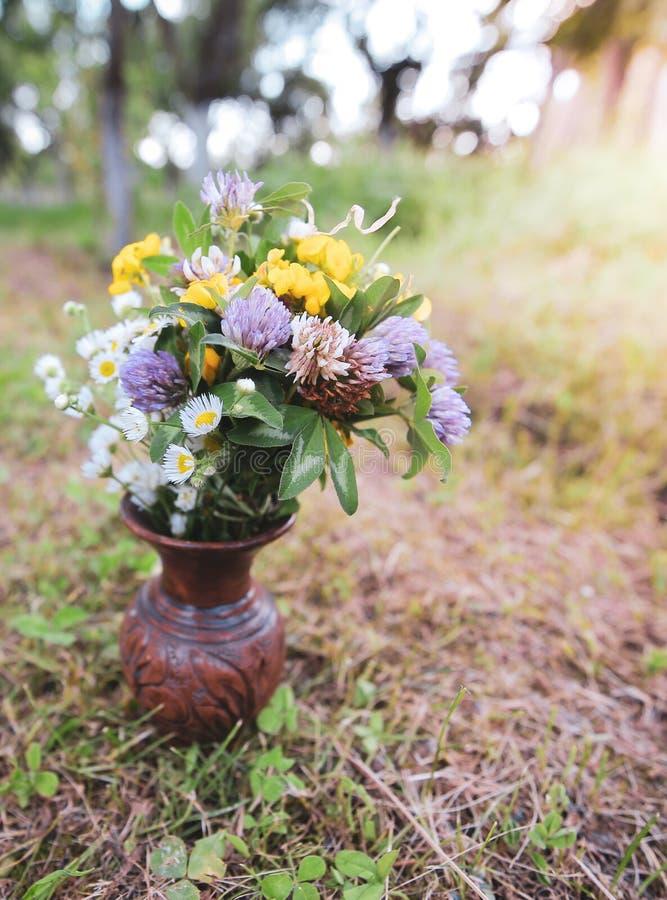 Bouquet des fleurs sauvages sauvages colorées dans un pot d'argile cassé étendu sur l'herbe photos stock