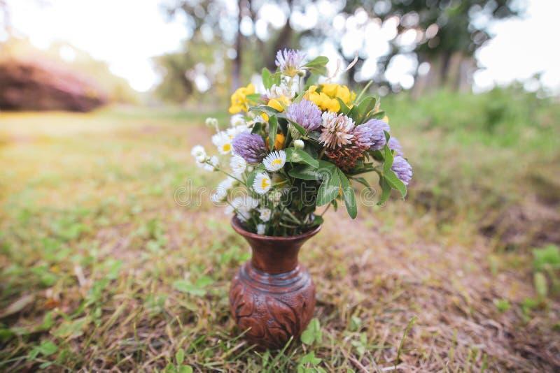 Bouquet des fleurs sauvages sauvages colorées dans un pot d'argile cassé étendu sur l'herbe photo stock