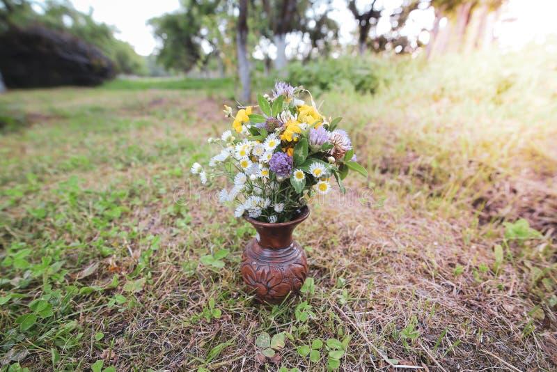 Bouquet des fleurs sauvages sauvages colorées dans un pot d'argile cassé étendu sur l'herbe photos libres de droits