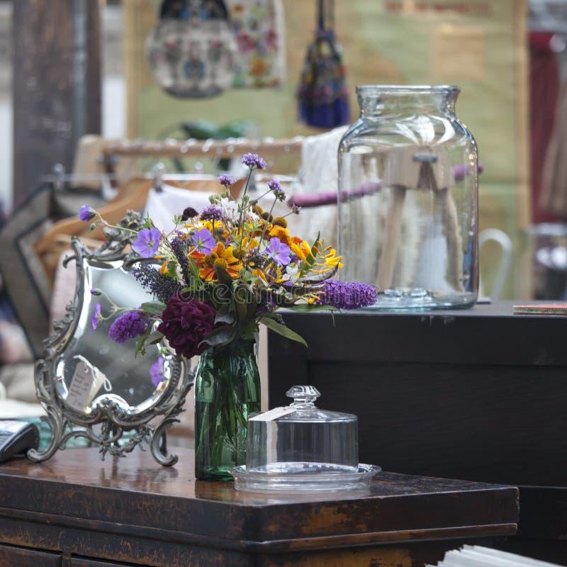 Bouquet des fleurs sauvages dans le pot vert sur la raboteuse dans le lit photographie stock