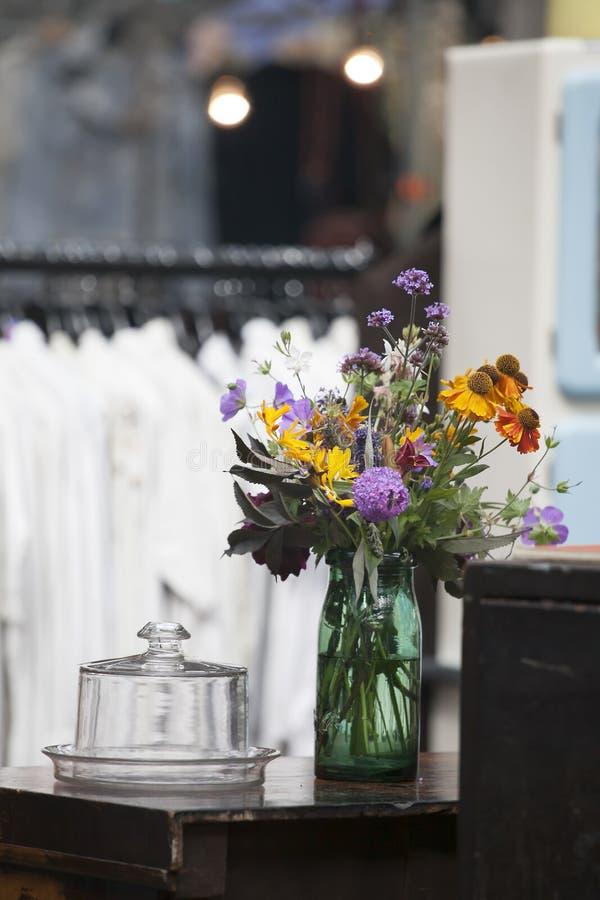 Bouquet des fleurs sauvages dans un pot vert sur la raboteuse dans le lit photographie stock libre de droits