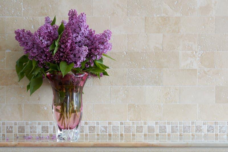 Bouquet des lilas dans le vase en verre sur le mur de fond du travertin Saveur des fleurs de ressort photographie stock