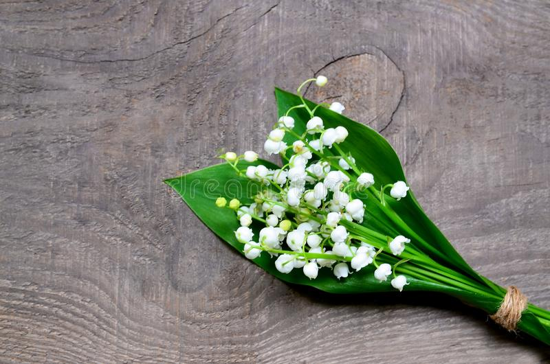 Bouquet des lis de la vallée sur le vieux fond en bois Fleurs de ressort du muguet Concept pour le jour ou l'anniversaire de Moth image stock