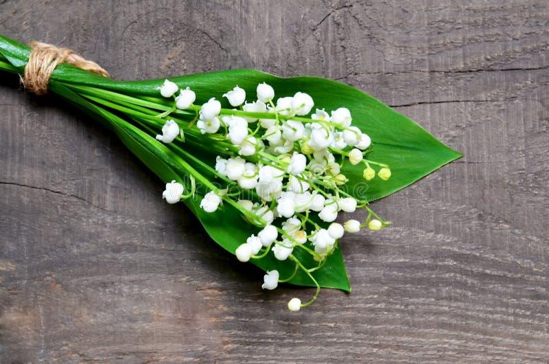 Bouquet des lis de la vallée sur le vieux fond en bois Fleurs de ressort du muguet Concept pour le jour ou l'anniversaire de Moth photographie stock