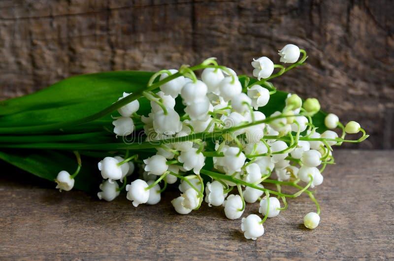Bouquet des lis de la vallée sur le vieux fond en bois Fleurs de ressort du muguet Concept pour le jour ou l'anniversaire de Moth images stock