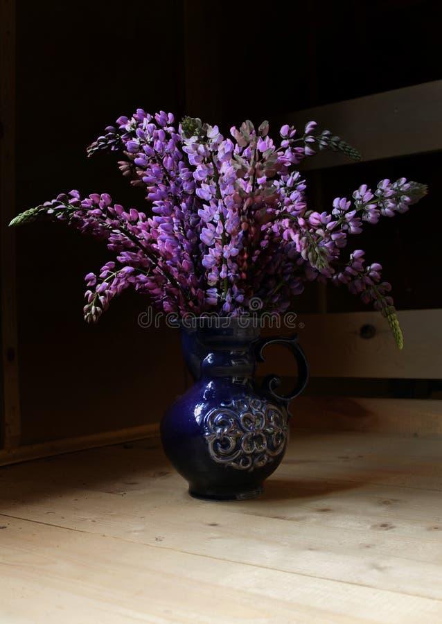 Bouquet des lupins dans un vase bleu sur un plancher en bois photos stock
