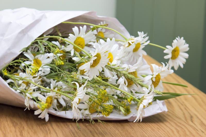 Bouquet des marguerites se trouvant sur une table en bois image stock