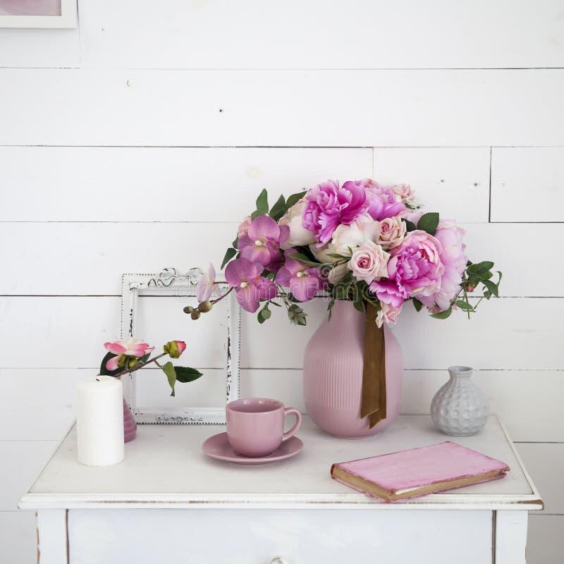 Bouquet des orchid?es, des pivoines, des roses dans un vase en c?ramique sur la table de chevet et d'une pile de livres image libre de droits