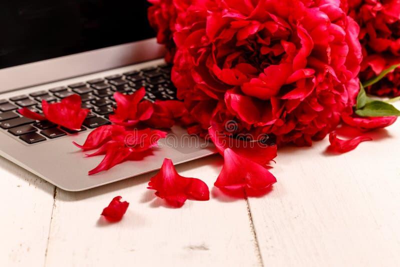 Bouquet des pivoines roses, de l'ordinateur portable, du smartphone, des stylos, des verres et d'un carnet sur une table blanche images stock