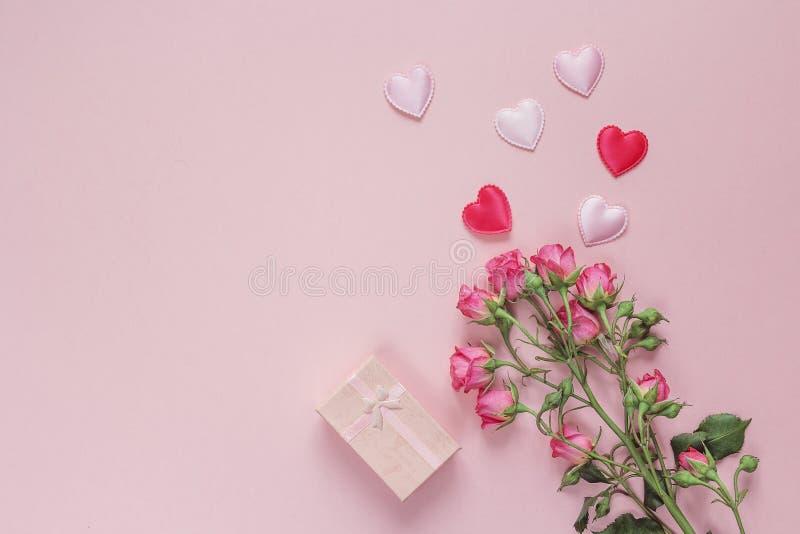 Bouquet des roses, du boîte-cadeau et des coeurs sur un fond rose Spac photo stock
